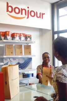 Total In a Total station's shop in Senegal, a customer gets the goods she purchased in a paper bag